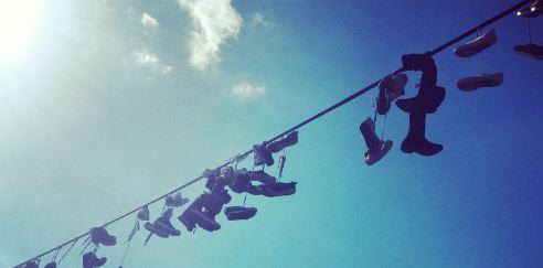tausende Paar Schuhe auf einem Stromdraht hängend