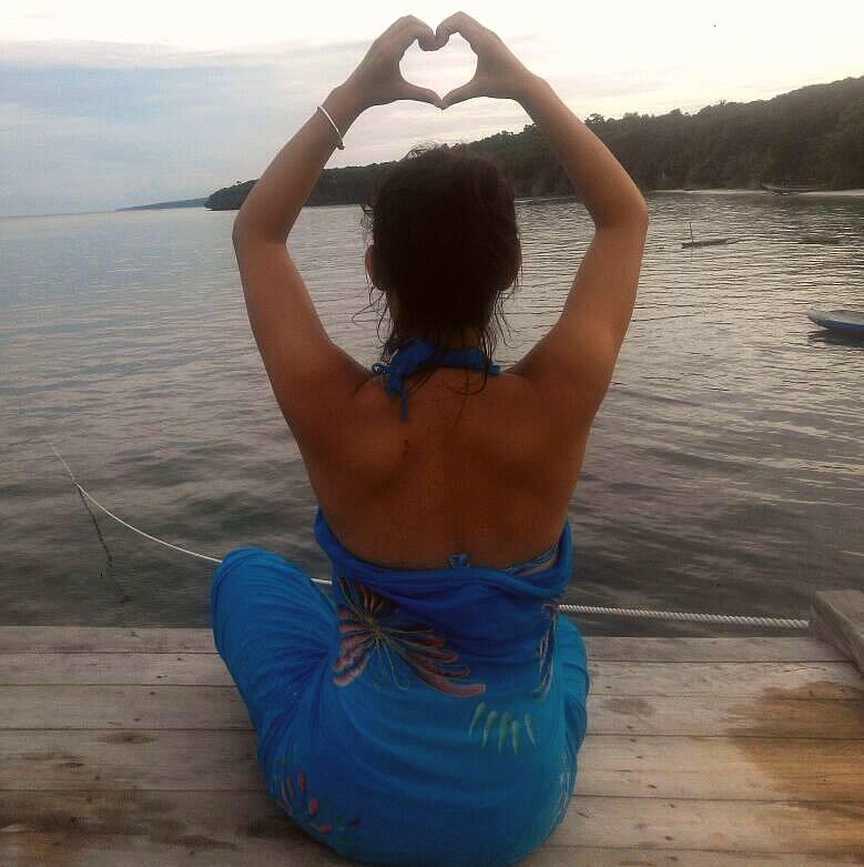 Sitzend auf einem Schiff, mit dem Rücken zur Kamera und ein Herzzeichen über dem Kopf mit beiden Händen geformt